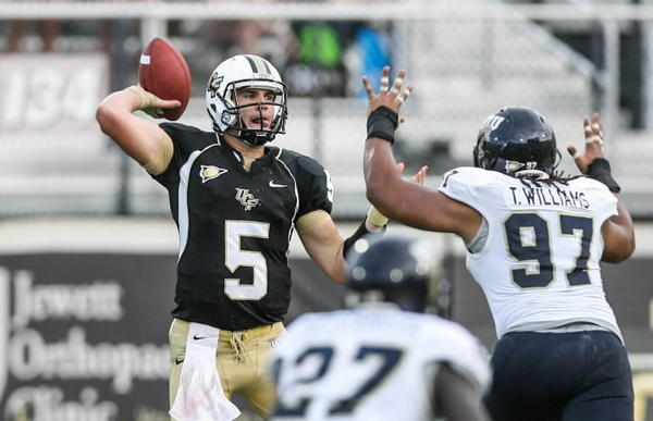 UCF quarterback Blake Bortles looks for a receiver under pressure from FIU's Tourek Williams (97) during the 4th quarter of the Knights' 33-20 conference victory against FIU at Bright House Networks Stadium in Orlando.