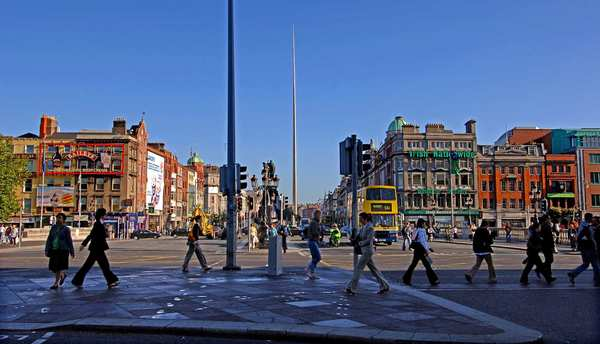 People walk along O'Connell Street before the Spire (on the site of the former Nelson's Pillar) as the day begins in Dublin.