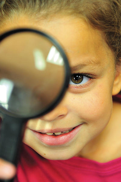 Greencastle-Antrim Primary School first-grader Safiyah Dahbi peers through a magnifying glass Tuesday as she and fellow students use new science center materials at the school.