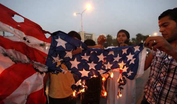 Protesters burn an American flag in Benghazi, Libya, where a mob this month killed four U.S. Americansl, including Ambassador J. Christopher Stevens.