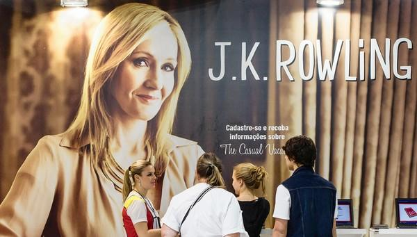 Visitors receive information on Brithish novelist J.K. Rowling's new book during the International Book Fair in Sao Paulo, Brazil in August.