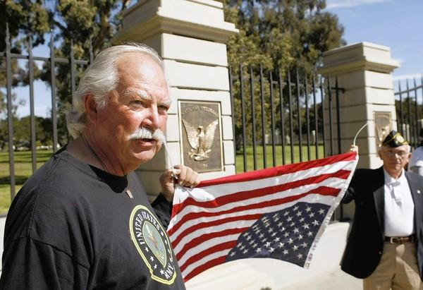 "Army vet Robert Rosebrock, 67, left, and fellow Army vet Ernie Hilger hold the American flag upside down as ""a symbol of distress"" outside the Veterans Affairs facility in West L.A."