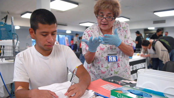 "Electrical technology student Ricardo Parada fills out an influenza vaccine form as registered nurse Yolanda ""Yoyo"" Smith, of Pioneers Memorial Hospital, explains the vaccine during the health fair at Imperial Valley College in Imperial on Tuesday."