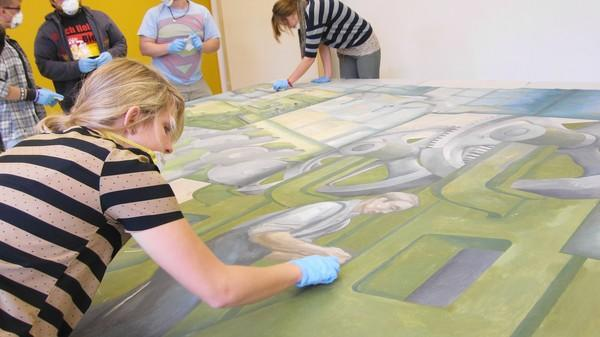 Judson University junior Emily Brosis and other students clean a 1940s mural that once hung in an old factory. The mural, owned by the Elgin Area Historical Museum, will hang in an art building on campus for at least the next three years.