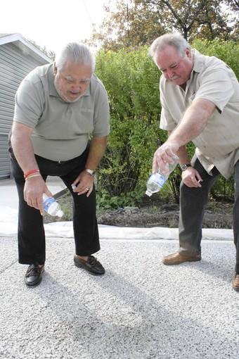 Des Plaines aldermen Mark Walsten, right, and Dick Sayad demonstrate how the newly constructed alley's permeable pavement absorbs water.