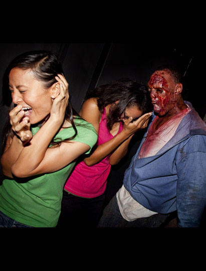 A zombie stalks visitors in the Walking Dead: Dead Inside maze during Halloween Horror Nights at Universal Studios Hollywood.