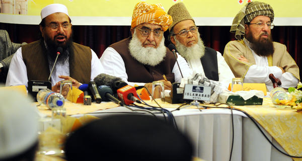 "Hafiz Mohammad Saeed, left, head of Pakistan's hard-line Islamic group of Jamaat ud Dawa, addresses a conference for the ""safeguarding the honor of the Prophet Mohammad"" in Islamabad on Tuesday. Muslim leaders demanded international action to stop religious insults in a challenge to President Barack Obama's defense of freedom of expression at the U.N. General Assembly."
