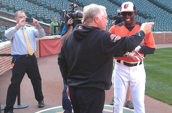Deion Sanders jokes around with Orioles manager Buck Showalter, who managed him in the Yankees' system years ago.