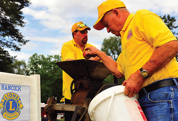 Scott McCusker, left, and Walter Buddy Dyer squeeze fresh apple cider at the 2011 Hancock Canal Apple Days. Below, bass player Doug Moats of The New Connection performs at the 2011 Canal Apple Days.