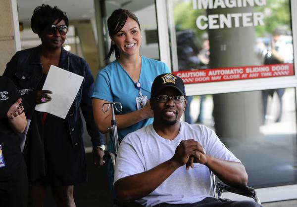 Chicago Police Officer Nyls Meredith is released from Advocate Christ Medical Center in Oak Lawn. Officer Meredith's wife Kimberly (left) walks in background. Meredith was wounded in a shootout last month while on-duty in the Morgan Park neighborhood.