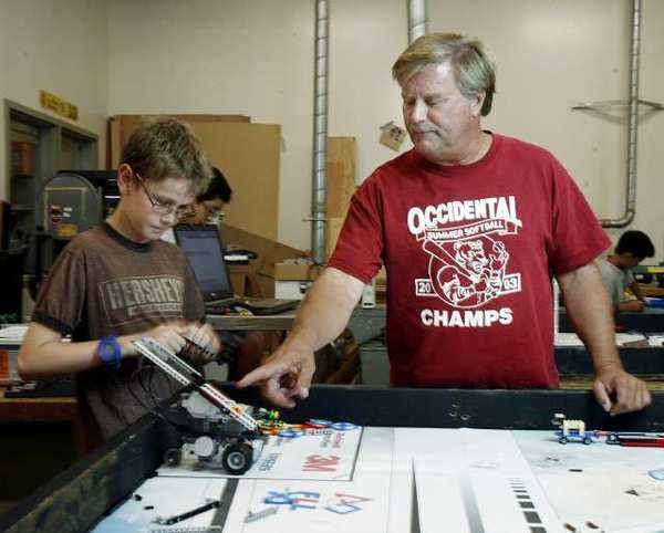Science teacher Steve Zimmmerman helps Micah Smyth, 11, of Palm Crest Elementary build his team's robot named Spartacus in the engineering lab at La Canada High School on Tuesday, September 25, 2012 with elementary and middle school students preparing robots for an October competition.