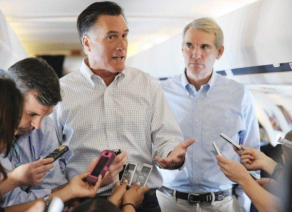 Mitt Romney speaks to reporters aboard his campaign plane as Ohio Senator Rob Portman, right, looks on while in flight to Denver.