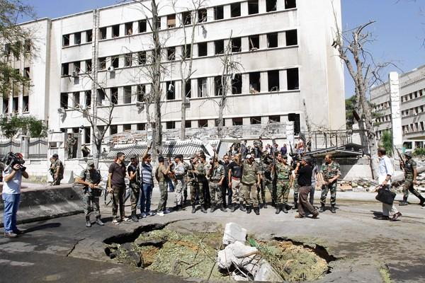 Syrian soldiers gather at the military headquarters in Damascus that came under rebel attack.