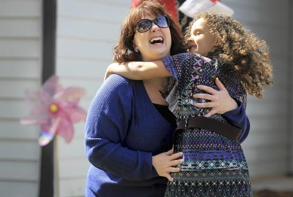 Diana Jensen hugs her daughter, Livia, 4, in front of their Aurora home on Wednesday.