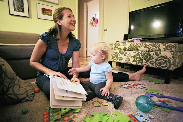 Sarah Lisle smiles as she looks up from her reading with her seventeen month old daughter Lily Lisle in Austin, Texas on September 13, 2012.