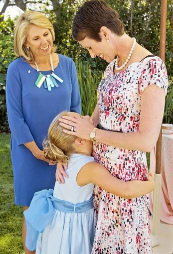 Breast cancer survivor Hollye Jacobs (CQ), right gets a hug from her daughter nicknamed Sweetly Six, bottom, as Carol Kurzig (CQ), left, President of Avon Foundation for Women in New York City looks on during a September Afternoon Tea Party at Jacobs's home in Santa Barbara Ca. as part of a fight against breast cancer on September 20,2012.