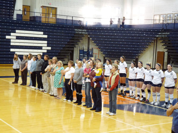 Former Petoskey High School volleyball players, coaches and parents line up for the national anthem prior to Wednesday's Big North Conference match against Gaylord during Title IX Night at the Petoskey High School gym.