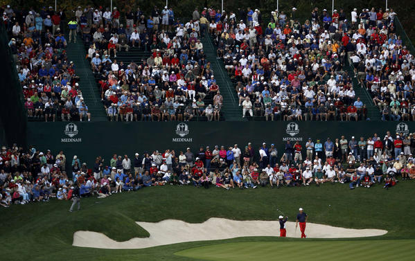Tiger Woods hits from a sand trap on the 17th hole next to Steve Stricker during a practice round at the 39th Ryder Cup, held at Medinah Country Club.