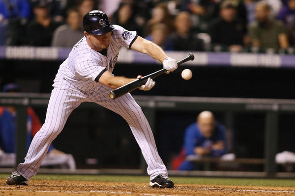 Colorado Rockies pitcher Alex White (6) lays down a bunt during the sixth inning against the Chicago Cubs.