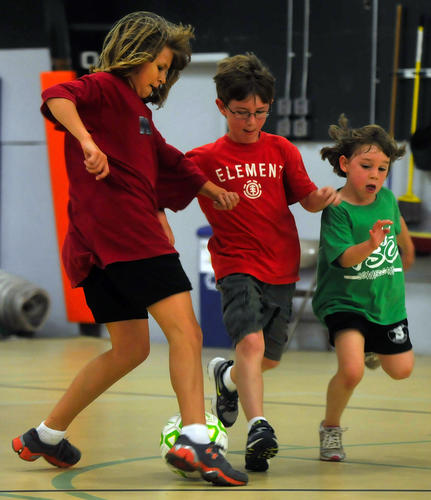 From left, Ingrid Peters, 10, Eric Wilken, 8, both of Avon and Nev Patterson, 6, of Simsbury, run for a loose ball during a soccer game during the camp.