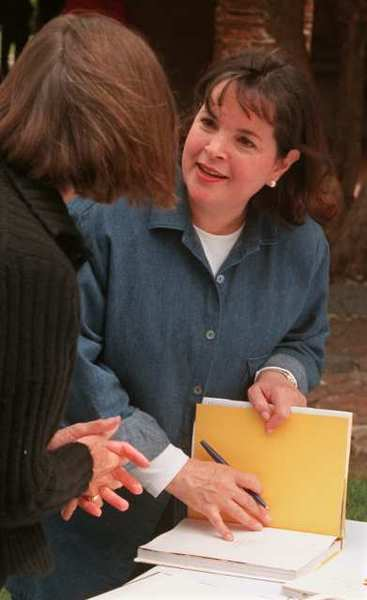 "Ina Garten, star of TV's ""The Barefoot Contessa,"" signs one of her cookbooks for a fan."