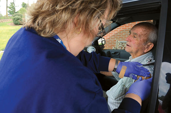 Clark Regional Medical Center nurse Karen Allen gives James Baker a flu shot Wednesday during the hospital's drive-through clinic at Rose Marcy C. Brooks Place.