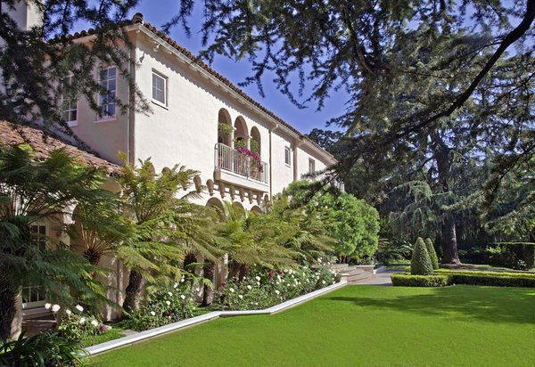 The 1920s house sits amid gardens, an expansive lawn and mature trees.