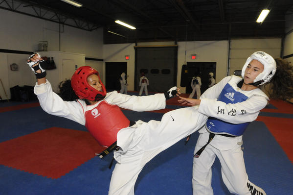 Kelsey Junious, 15, of South Windsor, left, a student of Tae Kwon Do, is heading to an international competiton representing the U.S. in Bolivia next month. She practices with Ceana Rodriguez at Styles United Transformative Martial Arts in South Windsor Wednesday night.
