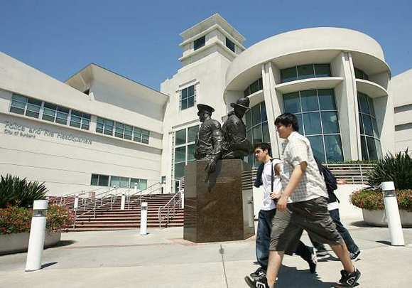Three pedestrians walk in front of the Burbank Police and Fire Headquarters in Downtown Burbank.