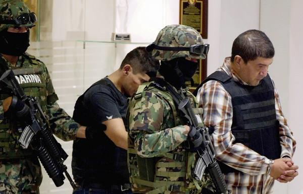 Ivan Velazquez Caballero, right, is escorted to a news conference in Mexico City a day after his arrest.
