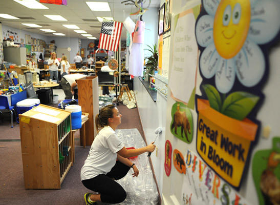 United Way volunteer Kristen Nonnemacher of the Crayola Factory helps paint one of the walls of the Spring Garden Children's Center in Easton, Thursday.