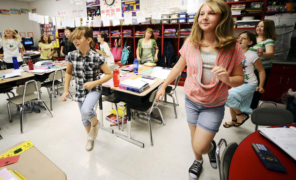 Mountain Ridge Intermediate School fourth-graders Isabelle Swigert (left) and Autumn Snyder (right) run in place during the JAM National Movement on Thursday morning at their school in Gerrardstown, W.Va.