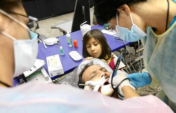 Julianna Rivera, 5, of Los Angeles, watches as her father, Julio Rivera, gets his teeth cleaned for the first time in three years at a free health clinic at the Los Angeles Spsorts Arena. Treating him are dental hygienist Stacey Leach, left, and Vanessa Shaw, a dental assistant student at American Career College.