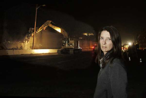 Kim Sandifer watches the demolition of the sound wall. Her family and their neighbors have complained to Caltrans and Metro about the early morning booming, the shaking,  the lights than make midnight seem like noon.