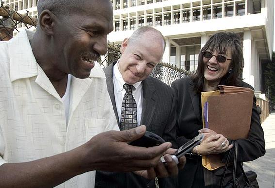 Willie Earl Green, left, marvels at a couple of cell phones with his attorneys Peter Camiel and Verna Wefald at his side.