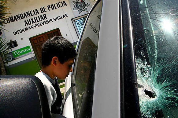 Outside a police station in the Colonia Libertad neighborhood of Tijuana, a boy peers into a police pickup damaged by gunfire.  One auxiliary policeman was slain and another wounded in the attack, one of a number across the city the night before by masked gunmen that left a total of seven officers dead, and two wounded. An additional officer was i