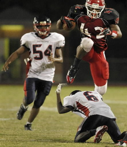 Hampton's Marshawn Williams jumps over Denbigh's Jaquan Jenkins to carry the ball during the second half of Thursday's game. Williams scored five touchdowns as the Crabbers won 42-0.