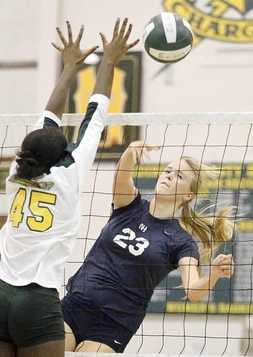 Newport Harbor High's Carolyn Bockrath (23) spikes the ball past Edison's Rayna Walker (45) during a Sunset League match.