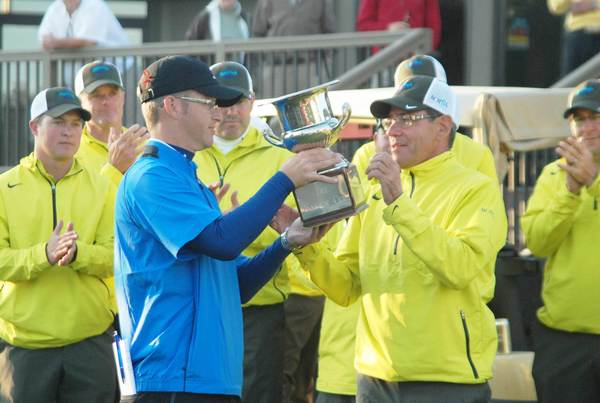 Team Harbor captain Shaun Bezilla presents Team Boyne captain Bernie Friedrich with the Harbor Cup last year after Team Boyne's victory, which ended a four-year Team Harbor win streak. The 2012 Harbor Cup is scheduled to begin Monday, Oct. 1, at Hidden River Golf & Casting Club in Brutus.
