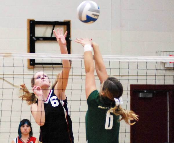 East Jordan's Angela Watkins (left) spikes the ball as Grayling's Makayla Cragg attempts the block Thursday.