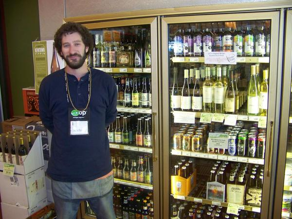 Michael Mann, beverage manager at the Grain Train in Petoskey, stands next to the beer cooler which is currently stocked with several fall specialties.