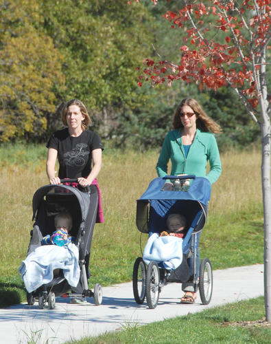 Sisters Katie Braendle (left) and Liz Doornbos, walk their children, Micah Braendle, 18 months and Noah Doornbos, 10 months, along the new Atkins Road corridor into North Central Michigan College, Thursday. The new roadway has been landscaped and features sidewalks on both sides of the street.
