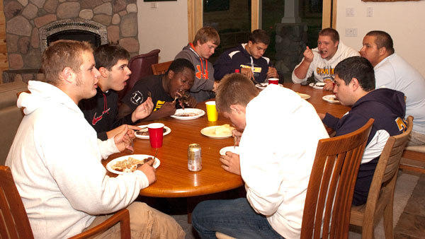 Blue Devil linemen, Dan Miller, Michael Skerratt, Blue Devil assistant coach Irving Lambert, Nick Kassuba, Nick Parker, Trevor Adams, Michael Shryock, Tyler Hagar and Blake Miller (bottom, l-r), chow down on steak as part of the weekly Hogfest where members of the team feast and talk.