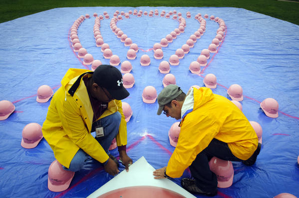 09.28.2012 - New Haven, CT - (L-R) Kevin Stokes and Serge Ghio prepare a tarp full of 160 pink hard hats in Amistad Park to become a human pink ribbon in recognition of October being Breast Cancer Awareness month. Photograph by MARK MIRKO  |  mmirko@courant.com
