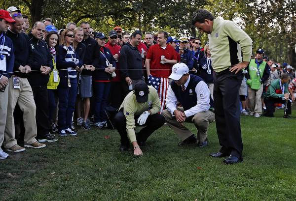 European Ryder Cup Team members Rory McIlroy, left, and teammate Graeme McDowell look at a ball buried in the grass on the eleventh fairway on the first day of competition at the 2012 Ryder Cup.