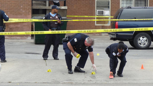 Chicago Police mark evidence at the scene where two men or boys were shot about 10:45 a.m. in the 6000 block of South Cottage Grove in the Woodlawn neighborhood of Chicago.