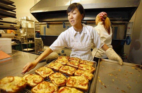 Na Young Ma, chef and owner of Proof Bakery, pulls some savory pastries from the giant oven.