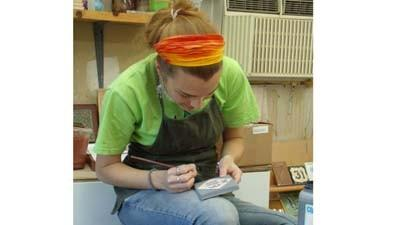 Cora Smith,design and production manager at Little Traverse Tileworks, applies a layer of underglaze to one of the company's ceramic tiles.