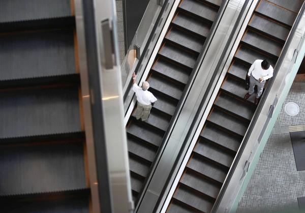 People ride an escalator inside a high-rise building in Tokyo August 31, 2012.