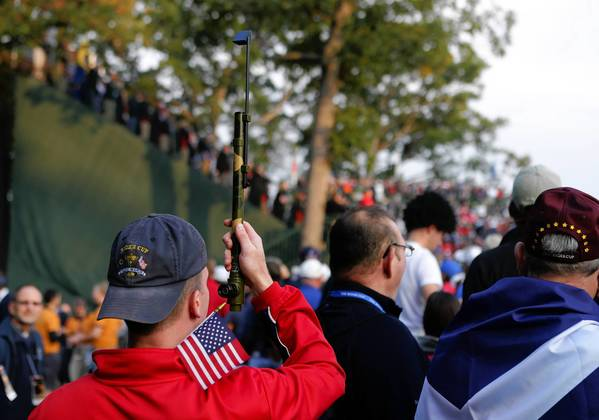A fan uses a periscope to get a view of the first tee box during the first round of the Ryder Cup at Medinah Country Club.